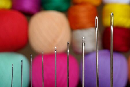 A set of needles for hand sewing on the background of colored threads. Sewing needle closeup