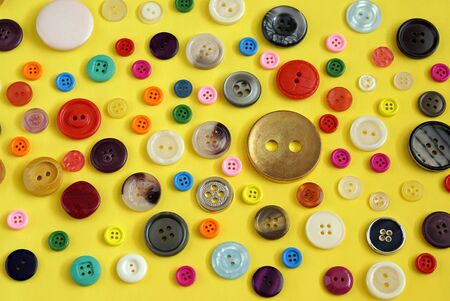 Collection of colorful sewing buttons on yellow background