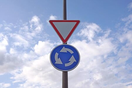 Traffic signs on blue sky background. Circular motion road sign and give way sign