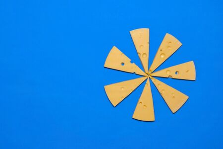 Slices of cheese on a blue background. Top view