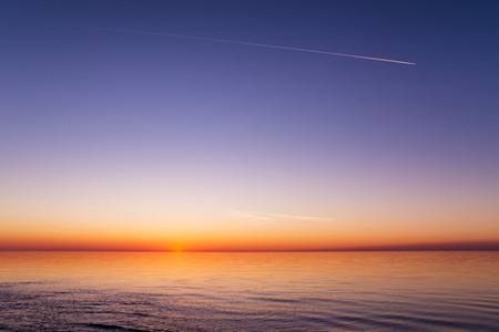 Beautiful view of the sunset over a sea with waves, ripples, clear sky and trace of a plane. Baltic sea, Latvia Banque d'images