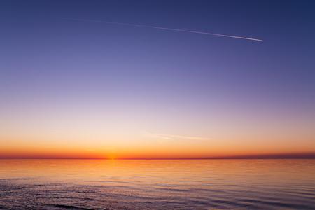 Hermosa vista de la puesta de sol sobre un mar con olas, ondulaciones, cielo claro y vestigios de un avión. mar Báltico, Letonia Foto de archivo - 46718133