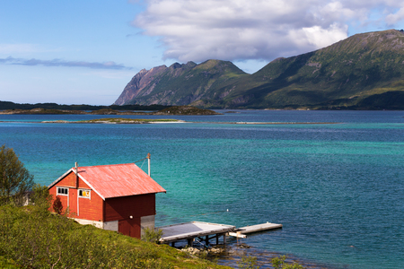 rorbu: Beautiful summer daylight view of Lofoten Islands, Norway, with mountains, fjord, and small red rorbu used as fishing lodge, and a pier.