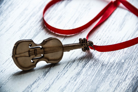 soprano saxophone: wooden violin with ribbon on wooden background music