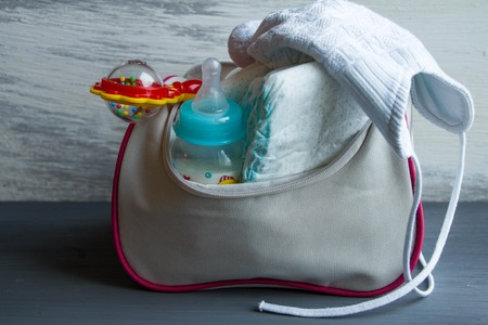 Womens handbag with items to care for the child: bottle of milk, disposable diapers, rattle, pacifier and baby clothes.