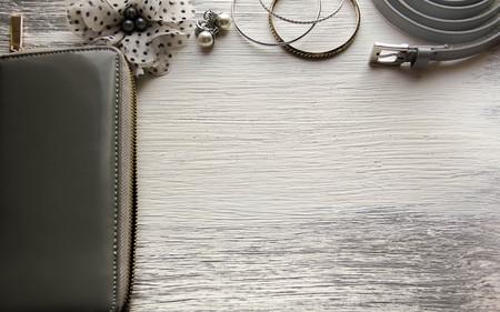 Essentials fashion woman objects on wooden background Female accessories: wallet bracelets earrings belt Stockfoto