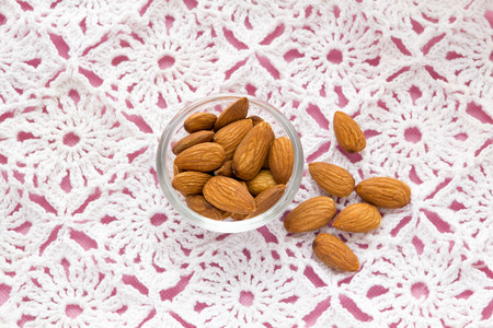 almond: almonds on pink tablecloth nuts useful products Stock Photo