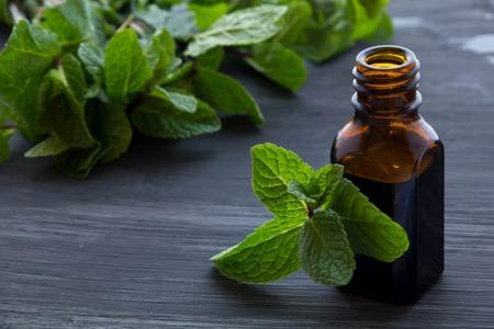 Wesentliche Aromaöl mit Pfefferminz auf Holzuntergrund. Standard-Bild