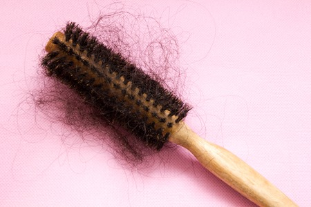 Hair brush with lost hair on it, on pink background Stock Photo