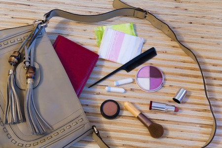 Things from the outdoor ladies handbag. womens purse on wood background. cosmetical shadows, varnishes, hygiene