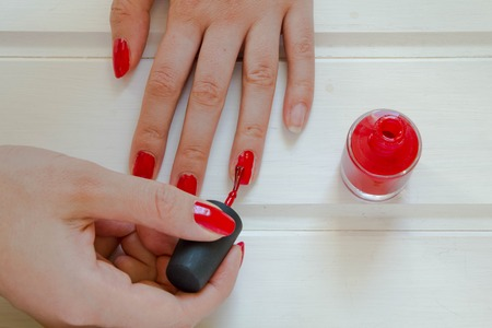 Woman applying red nail polish.  manicure on white background. Female hand. Stockfoto