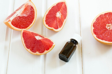 massage huile: L'huile essentielle dans une bouteille en verre avec des produits frais, de pamplemousse juteux. Spa concept. mise au point sélective.