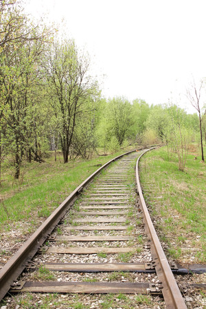 forest railway: View of an old abandoned railway track through a forest, Stock Photo
