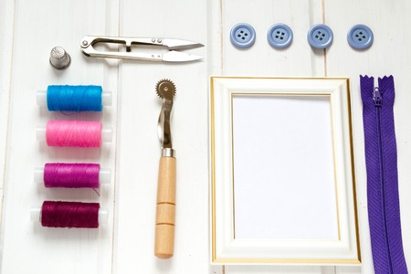 Vintage background with sewing accessories, tools, sewing kit. Scissors, bobbins with thread and needles on wooden white background