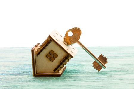 immovable: toy wooden model house as symbol family and love concept  on sunny old blue wooden background buying a house, mortgage, repair, stability Stock Photo