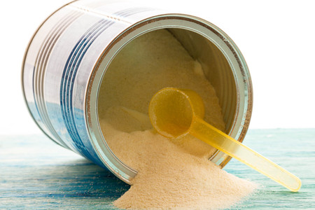 nappies: Powdered Milk, Baby Formula with spoon infant formula in can and bottle for feeding baby on blue wooden table. dairy food for baby  spilling out of a measuring scoop. Stock Photo