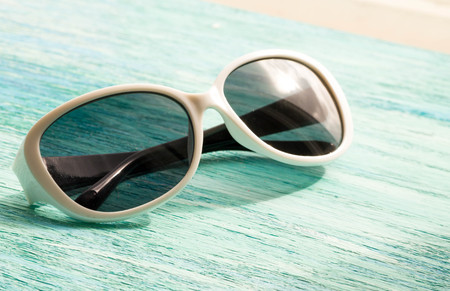 dismissal: Stylish white  sunglasses on the wooden background close up. horizontal summer concept. the dismissal, blue background, holiday Stock Photo