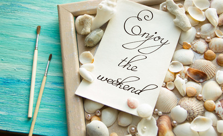 current events: Events Inspirational quote Enjot the weekend lettering on turquoise wooden background