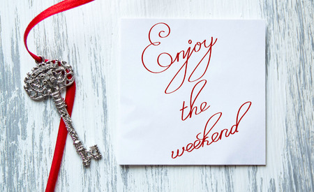 news current events: Inspirational quote Enjoy the weekend lettering on grey wooden background