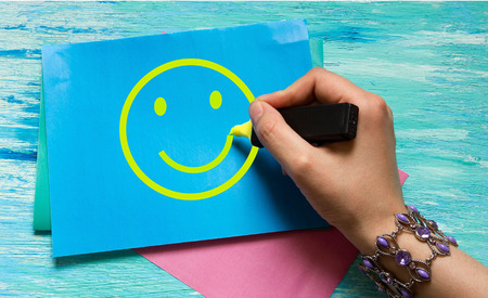 frame less: smiley womens hand drawing on a blue sheet with a yellow marker. the concept of happiness, good mood, can be used for ads, postcards