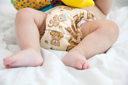 baby in modern eco stacks of cloth diapers and replacement bushings selective focus close-up on bright background