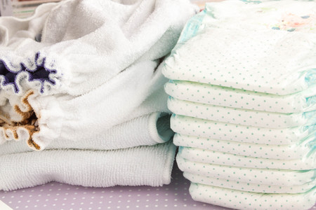 pampers: Modern eco stacks of cloth diapers and disposable diapers, pampers, close-up