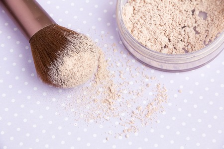 mineral Makeup powder and a powder brush on a purple background, soft bedding colors, close up