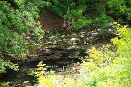 discarded: Illegal bulk waste discarded. Landfill in the river. polluted environment. Environment problem