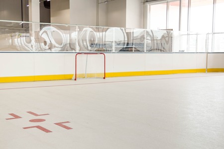face off: red line on hockey rink. Face off circle. modern empty rink. hockey goal. Front view from ice
