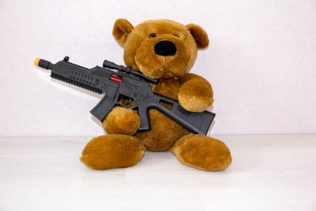 Teddy bear with toy gun. the concept war, child safety, terrorism, to protect children from armed attack, weapons ban, the peace of the world.