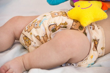 baby in modern eco stacks of cloth diapers and replacement bushings selective focus close-up bright background