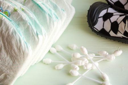 utiles de aseo personal: El juego de accesorios para pañales desechables para bebés en un árbol fondo azul turquesa, artículos para el cuidado del bebé. Lay panal del pañal, el padre el cuidado de bebé. bebé seguro palos del oído Foto de archivo