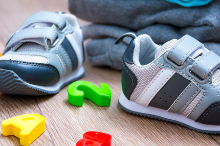 baby winter clothing, concept, autumn, sneakers, caps, toys. how to dress baby winter. choose the shoes.