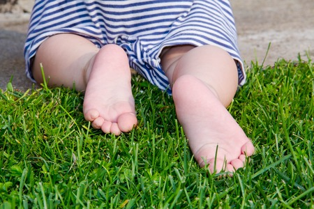 flatfoot: Child Feet Barefoot on Green Grass. Healthy Lifestyle. Spring Time. Rear view. the concept of flatfoot, the child is learning to crawl Close up. Stock Photo