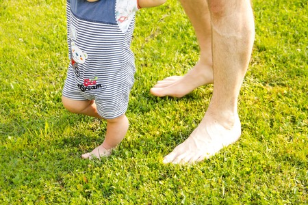 feel affection: father and young son. Closeup of how the supports the baby when he makes first steps. male hands holding small s . concept family