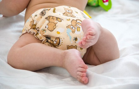 reusable: baby in modern eco stacks of cloth diapers and replacement bushings selective focus close-up bright background, little cute foot kid, the concept of health. hygiene of the child. reusable diapers