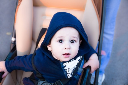 Een Warme Winter : Small cute newborn baby boy sitting in a carriage in warm winter