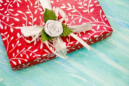 corporate event: Christmas Card red gift box with silver ribbon. party invitation corporate event decoration turquoise shabby table wooden background Top view, flat lay with copyspace slogan text message.