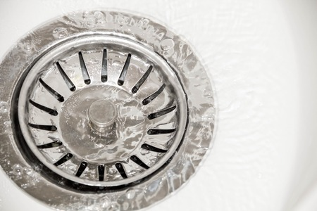 stainless steel sink: Stainless steel sink plug hole close up with water