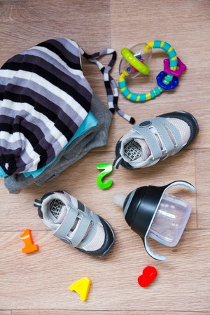 warm things: Autumn or winter childrens outfit clothes. Top view fashion trendy look of baby clothes with greeting card with cutest newborn baby and accessories for the fall or winter. Toning in warm color