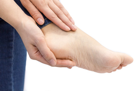 Pain in a foot. sports trauma. Woman cracked heels with white background, foot healthy concept. woman checks aching foot