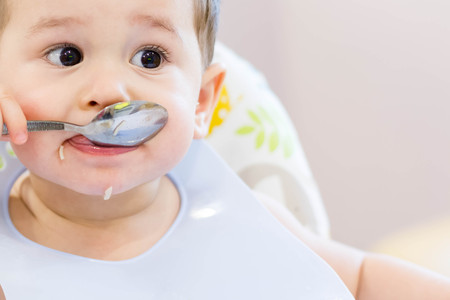 Closeup shot of a baby feeding with the spoon. The small child eats independently Archivio Fotografico