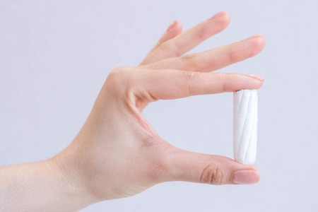 Womans hand holding clean cotton tampon close-up. Young woman preparing menstruation time. Soft tender protection woman critical days, gynecological. Medical hygiene conception and protection
