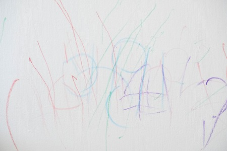 child painted abstract color on the wall. Childrens scribbles on the wall. crayons to Doodle on the white wall made the little child who could pass for abstract work.