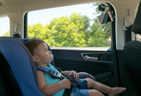 タブレットでの漫画を見ているチャイルド シートで車の中の男の子