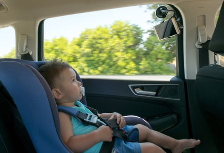 Baby boy in a car on child safety seat watching cartoon on the tablet Фото со стока