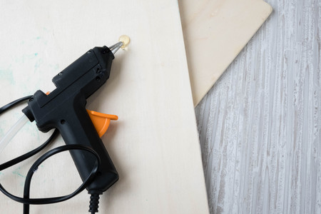 Electric hot glue gun on a wood background. the concept of repair or creativity background