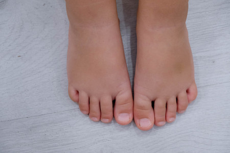 Childrens bare feet. Childs bare feet on the wooden floor