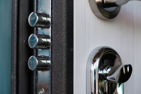 Open door of a family home. Close-up of the lock with your keys on an armored door. Security. Key cylinder, close up photo. door lock. The door lock with keys in situation it is closed