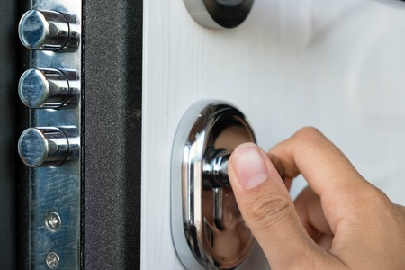 Open door of a family home. Close-up of the lock with your keys on an armored door. Security. Key cylinder, close up photo. door lock. The door lock with keys in situation it is closed.